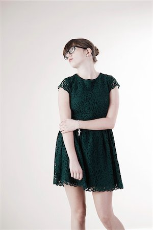 Portrait of Young Woman wearing Green, Lace Dress and Horn-rimmed Eyeglasses, Distracted and Looking Upward, Studio Shot on White Background Stock Photo - Premium Royalty-Free, Code: 600-06486279