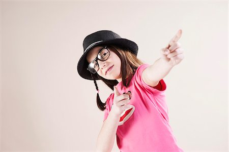 Portrait of Girl wearing Fedora and Horn-rimmed Eyeglasses, Pointing and Smiling at Camera, Studio Shot on White Background Stock Photo - Premium Royalty-Free, Code: 600-06486284
