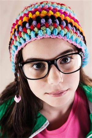 preteen girls faces photo - Close-up Portrait of Girl wearing Woolen Hat and Horn-rimmed Eyeglasses, Looking at Camera, Studio Shot on White Background Stock Photo - Premium Royalty-Free, Code: 600-06486286