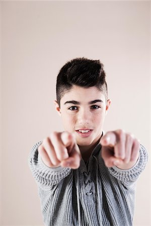 focus on background - Portrait of Boy Pointing at Camera in Studio Stock Photo - Premium Royalty-Free, Code: 600-06486396