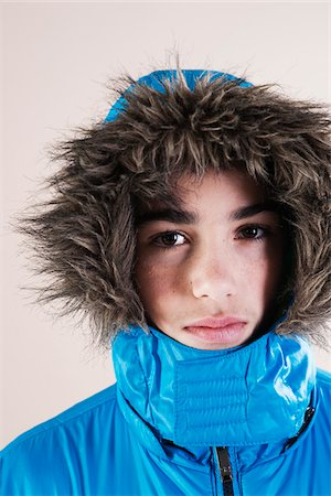 Portrait of Boy in Winter Jacket with Faux Fur Trimmed Hood in Studio Stock Photo - Premium Royalty-Free, Code: 600-06486426