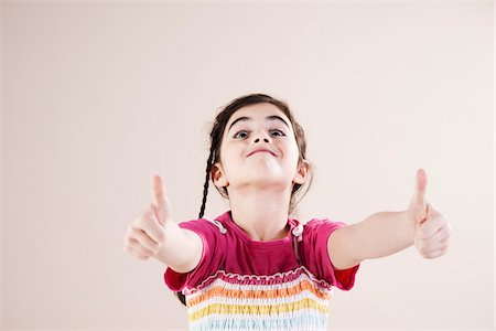 Portrait of Girl giving Thumbs up in Studio Stock Photo - Premium Royalty-Free, Code: 600-06486423