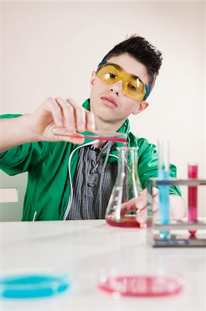 Boy wearing Safety Glasses Pouring Liquid from Test Tube into Beaker, Mannheim, Baden-Wurttemberg, Germany Stock Photo - Premium Royalty-Free, Code: 600-06486448