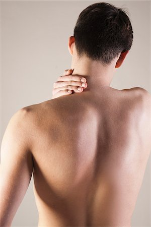 Close-up, Backview of Young Man Rubbing Neck with Hand, Studio Shot Stock Photo - Premium Royalty-Free, Code: 600-06505865