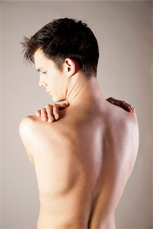 Close-up, Backview of Young Man Rubbing Shoulders with Hands, Studio Shot Stock Photo - Premium Royalty-Free, Code: 600-06505868