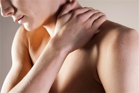 Close-up of Young Man Rubbing Shoulder with Hand, Studio Shot Stock Photo - Premium Royalty-Free, Code: 600-06505869