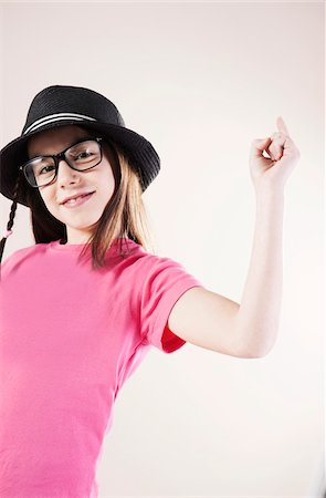 preteens fingering - Portrait of Girl wearing Fedora and Horn-rimmed Eyeglasses, Smiling at Camera, Studio Shot Stock Photo - Premium Royalty-Free, Code: 600-06505874