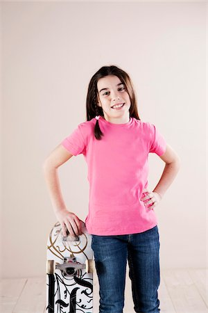 preteen girl pigtails - Portrait of Girl Standing and Leaning on Skateboard, Smiling at Camera, Studio Shot Stock Photo - Premium Royalty-Free, Code: 600-06505875