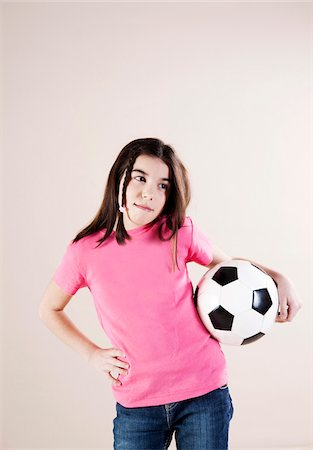 preteen girl pigtails - Portrait of Girl with Hand on Hips and Holding Soccer Ball, Looking to the Side, Studio Shot Stock Photo - Premium Royalty-Free, Code: 600-06505876