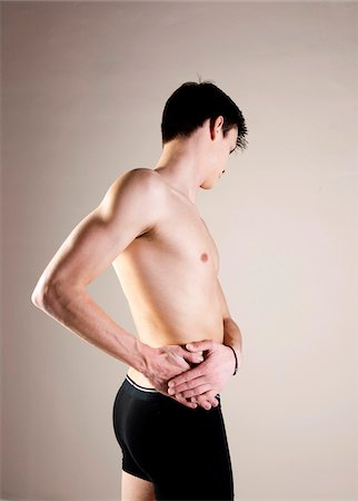 Side View of Young Man wearing Underwear and Holding Hip with Hands, Studio Shot Stock Photo - Premium Royalty-Free, Code: 600-06505871