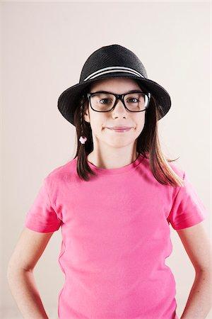 Portrait of Girl wearing Fedora and Horn-Rimmed Eyeglasses, Looking at Camera, Studio Shot Stock Photo - Premium Royalty-Free, Code: 600-06505873