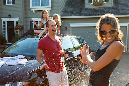 A family washes their car in the driveway of their home on a sunny summer afternoon in Portland, Oregon, USA Stock Photo - Premium Royalty-Free, Code: 600-06531436