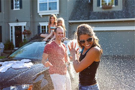A family washes their car in the driveway of their home on a sunny summer afternoon in Portland, Oregon, USA Stock Photo - Premium Royalty-Free, Code: 600-06531437