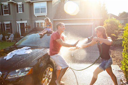 A family washes their car in the driveway of their home on a sunny summer afternoon in Portland, Oregon, USA Stock Photo - Premium Royalty-Free, Code: 600-06531438