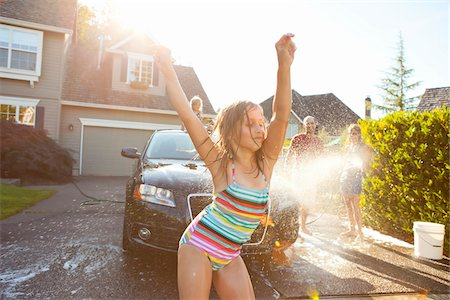 preteen bathing suit - Young girl dances while family washes car in the driveway of their home on a sunny summer afternoon in Portland, Oregon, USA Stock Photo - Premium Royalty-Free, Code: 600-06531439