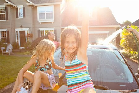 A family washes their car in the driveway of their home on a sunny summer afternoon in Portland, Oregon, USA Stock Photo - Premium Royalty-Free, Code: 600-06531430