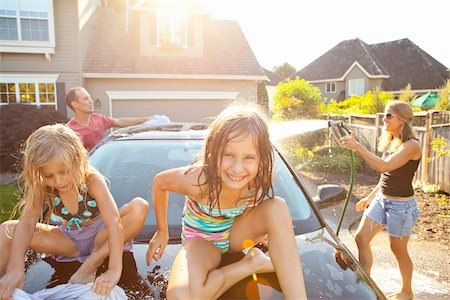 A family washes their car in the driveway of their home on a sunny summer afternoon in Portland, Oregon, USA Stock Photo - Premium Royalty-Free, Code: 600-06531431