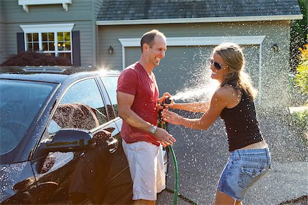 Couple washing their car in the driveway of their home on a sunny summer afternoon in Portland, Oregon, USA Stock Photo - Premium Royalty-Free, Code: 600-06531433