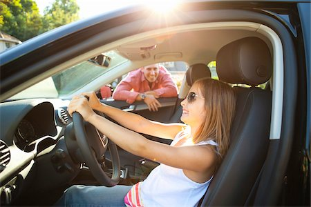 Young girl sitting in driver's seat of car, pretending to be old enough to drive as her smiling father watches on on a sunny summer evening in Portland, Oregon, USA Stock Photo - Premium Royalty-Free, Code: 600-06531446