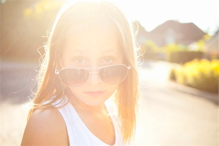 preteen girl - Portrait of young girl wearing aviator sunglasses on a sunny summer evening in Portland, Oregon, USA Stock Photo - Premium Royalty-Free, Code: 600-06531447