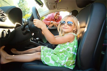Portrait of little girl sitting in driver's seat of car, pretending to be old enough to drive as her smiling father watches on on a sunny summer evening in Portland, Oregon, USA Stock Photo - Premium Royalty-Free, Code: 600-06531449