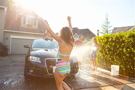 preteen swimsuit - Young girl dances while family washes their car in the driveway of their home on a sunny summer afternoon in Portland, Oregon, USA Stock Photo - Premium Royalty-Free, Code: 600-06531440