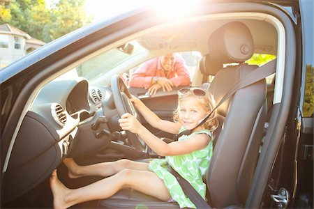 Little girl sitting in driver's seat of car wearing seatbelt, pretending to be old enough to drive and showing she knows the importance of a seat belt as her smiling father watches on on a sunny summer evening in Portland, Oregon, USA Stock Photo - Premium Royalty-Free, Code: 600-06531450