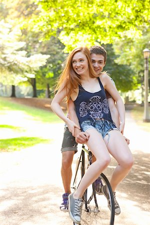 Young couple riding bike together in a park on a warm summer day in Portland, Oregon, USA Stock Photo - Premium Royalty-Free, Code: 600-06531452