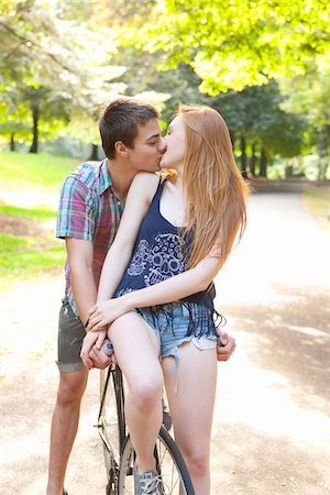 Young couple riding bike together in a park on a warm summer day in Portland, Oregon, USA Stock Photo - Premium Royalty-Free, Code: 600-06531453