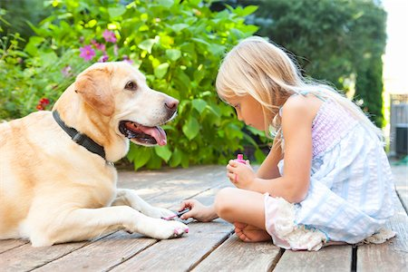 Little girl painting the claws of a dog with bright pink nail polish on a sunny summer afternoon in Portland, Oregon, USA Stock Photo - Premium Royalty-Free, Code: 600-06531467