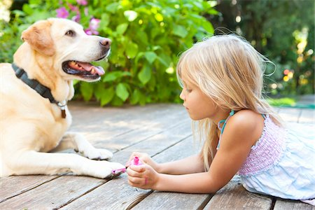 Little girl painting the claws of a dog with bright pink nail polish on a sunny summer afternoon in Portland, Oregon, USA Stock Photo - Premium Royalty-Free, Code: 600-06531468