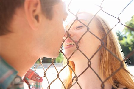Young couple kissing through chain link fence in park near the tennis court on a warm summer day in Portland, Oregon, USA Stock Photo - Premium Royalty-Free, Code: 600-06531460