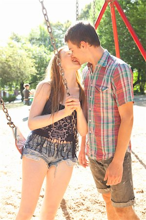 Young couple on swingset in park, kissing on a warm summer day in Portland, Oregon, USA Stock Photo - Premium Royalty-Free, Code: 600-06531462