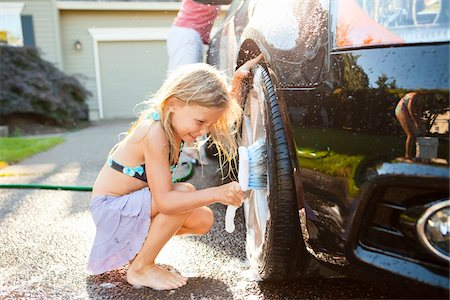 preteen swimsuit - Young daughters help father wash their car in the driveway of their home on a sunny summer afternoon in Portland, Oregon, USA Stock Photo - Premium Royalty-Free, Code: 600-06531474