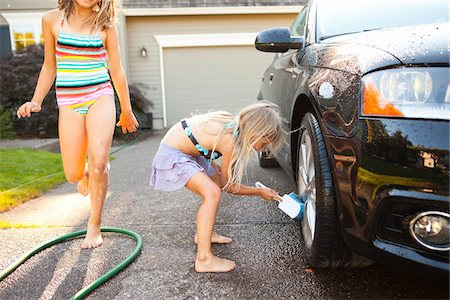 Sisters washing car in the driveway of their home on a sunny summer afternoon in Portland, Oregon, USA Stock Photo - Premium Royalty-Free, Code: 600-06531471
