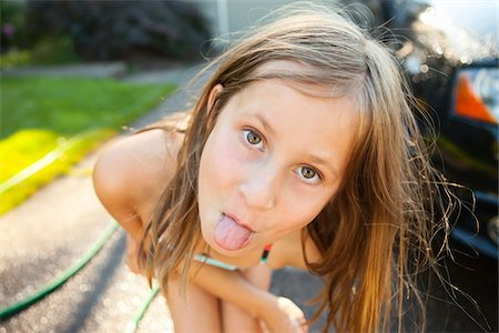 preteen girls faces photo - Portrait of young girl sticking her tongue out while washing car in the driveway of their home on a sunny summer afternoon in Portland, Oregon, USA Stock Photo - Premium Royalty-Free, Code: 600-06531472