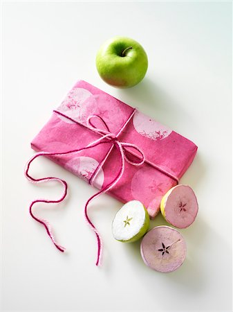 stamp (imprinted mark) - Gift, Craft demonstration of how to use granny smith apples cut in half and dipped in pink and white paint to make wrapping paper Stock Photo - Premium Royalty-Free, Code: 600-06531986