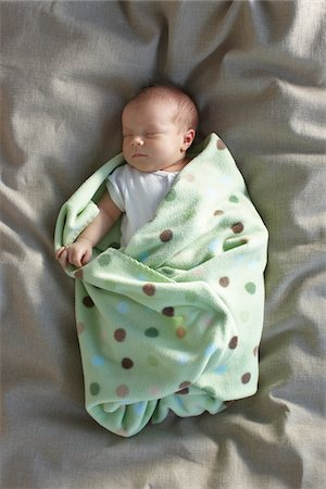 newborn baby girl in a white undershirt sleeping on a bed swaddled in a baby blanket, Ontario, Canada Stock Photo - Premium Royalty-Free, Code: 600-06531988