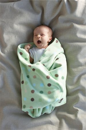 newborn baby girl in a white undershirt yawning on a bed swaddled in a baby blanket Stock Photo - Premium Royalty-Free, Code: 600-06531991