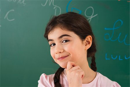 Girl with Hand on Chin in Front of Chalkboard in Classroom Stock Photo - Premium Royalty-Free, Code: 600-06543498