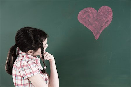 drawing - Girl with Hand on Chin Looking at Heart Drawing on Chalkboard in Classroom Stock Photo - Premium Royalty-Free, Code: 600-06543533