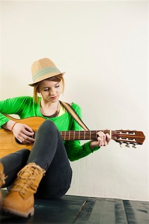 Portrait of Teenage Girl Sitting on Floor, Wearing Hat and Playing Acoustic Guitar, Studio Shot on White Background Stock Photo - Premium Royalty-Free, Code: 600-06553414