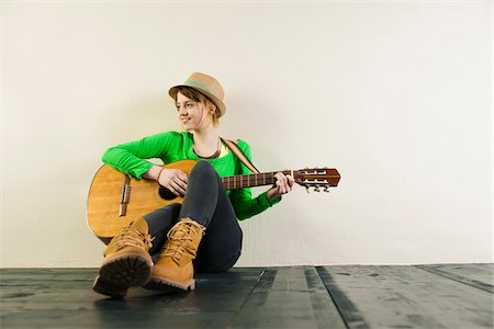 practise - Portrait of Teenage Girl Sitting on Floor, Wearing Hat and Playing Acoustic Guitar, Studio Shot on White Background Stock Photo - Premium Royalty-Free, Code: 600-06553415