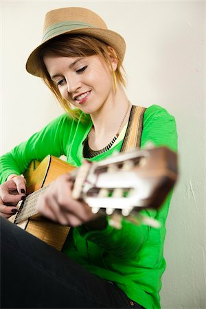Portrait of Teenage Girl Wearing Hat and Playing Acoustic Guitar, Studio Shot on White Background Stock Photo - Premium Royalty-Free, Code: 600-06553416