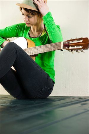 Portrait of Teenage Girl Sitting on Floor, Wearing Hat and holding Acoustic Guitar, Studio Shot on White Background Stock Photo - Premium Royalty-Free, Code: 600-06553417