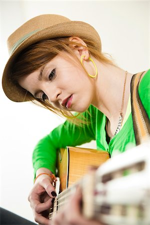 Close-up Portrait of Teenage Girl Wearing Hat and Playing Acoustic Guitar, Studio Shot on White Background Stock Photo - Premium Royalty-Free, Code: 600-06553418