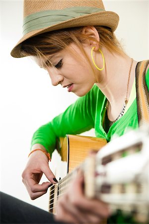 Close-up Portrait of Teenage Girl Wearing Hat and Playing Acoustic Guitar, Studio Shot on White Background Stock Photo - Premium Royalty-Free, Code: 600-06553419