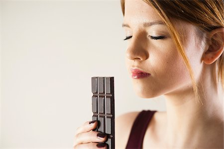 smelling - Teenage Girl holding Chocolate with Eyes Closed, Studio Shot on White Background Stock Photo - Premium Royalty-Free, Code: 600-06553410