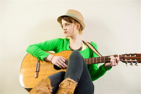 Portrait of Teenage Girl Wearing Hat and Playing Acoustic Guitar, Studio Shot on White Background Stock Photo - Premium Royalty-Free, Code: 600-06553413