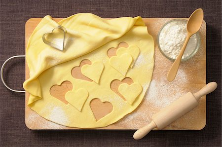 sweets - Overhead View of Hearts cut out of Cookie Dough with Rolling Pin, Wooden Spoon and Bowl of Flour Stock Photo - Premium Royalty-Free, Code: 600-06553485